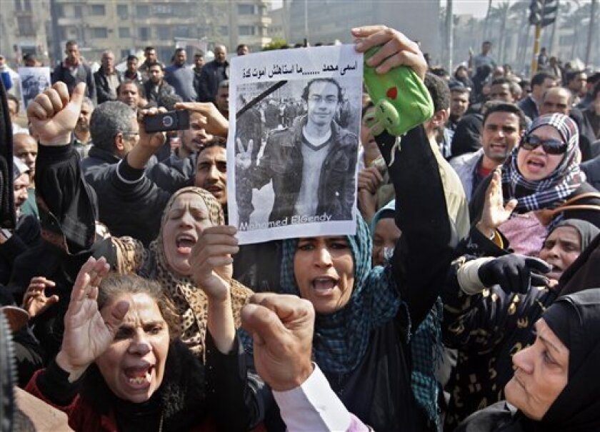 """Egyptian relatives of Mohammed el-Gindy, a 28-year-old activist, who died early Monday of wounds sustained during clashes last Friday near the presidential palace, display his picture as they shout anti-president Morsi slogans during his funeral procession in Tahrir Square, Cairo, Egypt, Monday, Feb. 4, 2013. More than 60 people have died in recent protests across Egypt that began on Thursday, Jan. 24, 2013, the eve of the second anniversary of the start of the uprising that toppled autocrat Hosni Mubarak. Arabic reads """"my name is Mohammed and I did not deserve to die this way."""" (AP Photo/Amr Nabil)"""