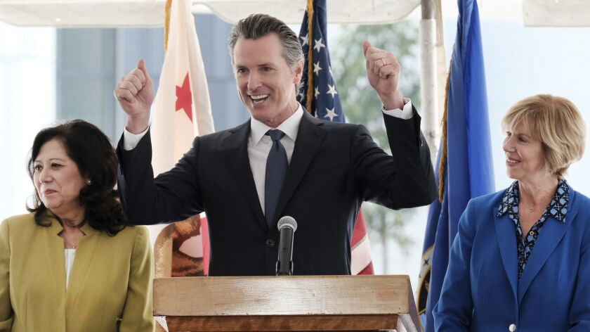 Gov. Gavin Newsom speaks at a news conference Wednesday flanked by L.A. County Supervisors Hilda Solis, left, and Janice Hahn at Rancho Los Amigos National Rehabilitation Center in Downey.