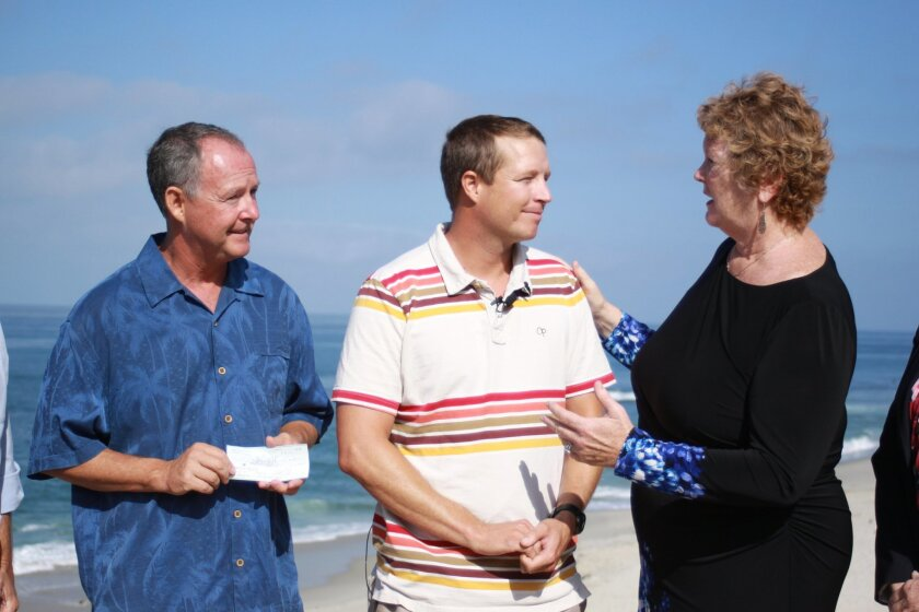 "Lifeguard Association spokesperson Ed Harris and Gareth ""Chappy"" Chapman with city councilmember Marti Emerald. Emerald presented Harris with a check to kick-off the fundraising for the SDLG Relief Fund."