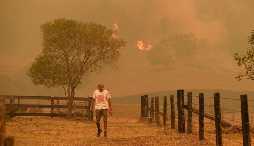 An Australian man walks on a farm Nov. 14 in the New South Wales town of Taree as a bushfire nears.