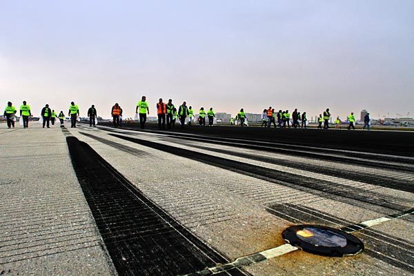 Los Angeles International Airport personnel wearing safety vests or bright-colored T-shirts take part in the first runway walk, picking up debris to clear Runway 24R on the north side of the airport.