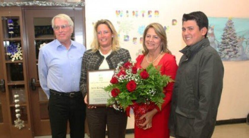 "Town Council President Cindy Greatrex (second from left) honors Ann Kerr Bache with a plaque for her work as chair of the La Jolla Christmas Parade and Holiday Festival. ""I couldn't do what I've been doing for 16 years without my husband, Tom (far left), and my son, David (far right),"" she said. To"
