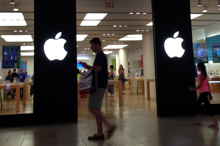 A shopper walks by an Apple store in Peabody, Mass., Monday, June 9, 2014. Apple's resurgent stock may have as much to do with financial engineering as the company's technological wizardry. In late April, the iPhone and iPad maker announced plans to split its stock for the first time in nine years. Since then, Apple's stock has climbed 23 percent, creating more than $100 billion in shareholder wealth while the Standard & Poor's 500 edged up just 4 percent. (AP Photo/Elise Amendola)