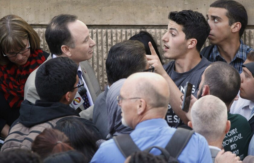 San Diego State student Osama Alkhawaja, gesturing, whose name was on a flier saying he was a terrorist, and SDSU president Dr. Elliot Hirshman, left, have a conversation while surrounded by students, who are protesting over how San Diego State University administrators have handled recent fliers b