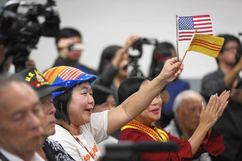 Victoria Kim waves the flags of the U.S. and the former South Vietnam during a town hall meeting with the U.S. ambassador to Vietnam, Ted Osius, at Coastline Community College in Little Saigon.