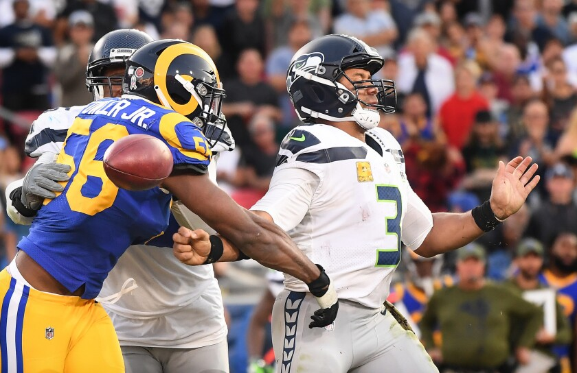 Rams linebacker Dante Fowler forces a fumble by Seattle Seahawks quarterback Russell Wilson in thefourthquarter of their game at the Coliseum last season, a key play in L.A.'s 36-31 victory.