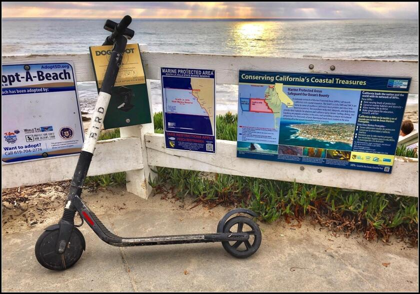 "This shows the Windansea Beach scooter abuse I observed on Aug. 5, 2019 in La Jolla. The ""Adopt a Beach"" slogan seems to have been co-opted by scooter pollution. Even better is the ""Conserving California's Coastal Treasures"" sign punctuated by the abandoned scooter. — Cliff Oliver"
