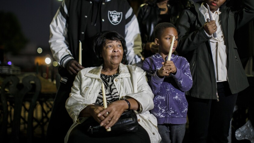 Ruth Harlins, seated, is joined by family and community members at a candlelight vigil for her daughter Denise Harlins in Los Angeles on Wednesday. Denise Harlins died this week.