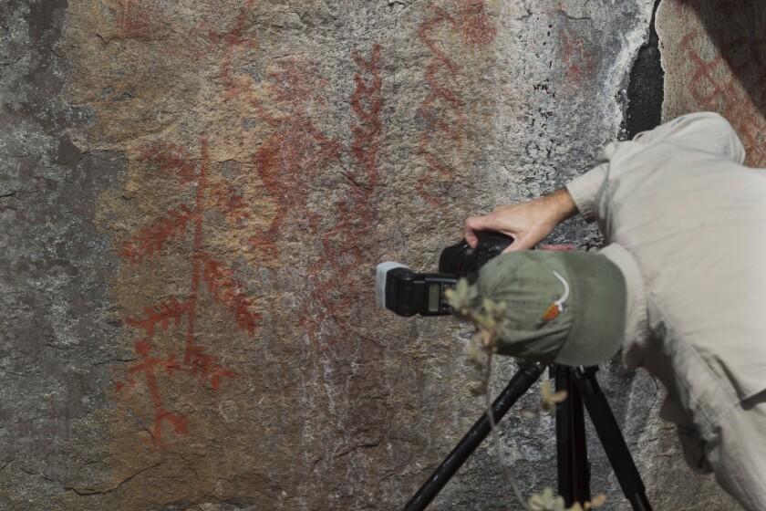 Indigenous rock art expert Steve Freer is shown photographing the main figures of rock art
