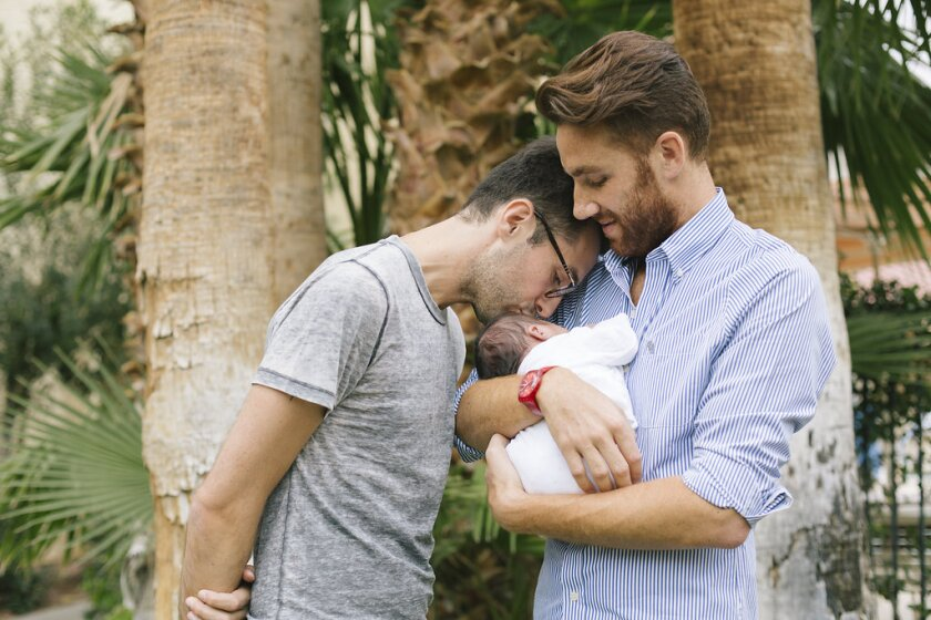 """A man cradles a baby as his husband kisses the child's forehead in the documentary """"Ghosts of the République."""""""