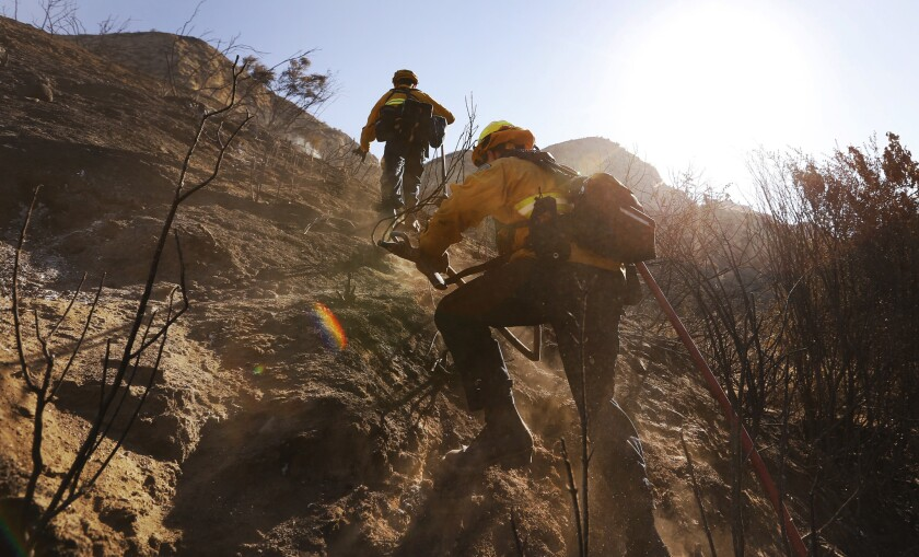 Firefighters John Kafoury, left, and Matt Petro with the Orange County Fire Authority assist Los Angeles County firefighters working to gain containment of a wildfire that is burning in the Placerita Canyon area of Santa Clarita.