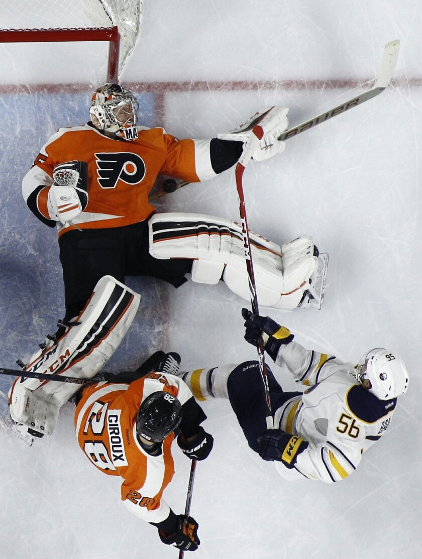 Philadelphia Flyers' Steve Mason, top, blocks a shot by Buffalo Sabres' Justin Bailey, right, as Claude Giroux defends during the first period of an NHL hockey game, Thursday, Feb. 11, 2016, in Philadelphia. (AP Photo/Matt Slocum)