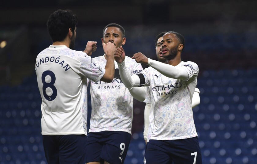 Manchester City's Raheem Sterling, right, celebrates with teammates after scoring his side's second goal during the English Premier League soccer match between Burnley and Manchester City at Turf Moor stadium in Burnley, England, Wednesday, Feb. 3, 2021. (Gareth Copley/Pool via AP)