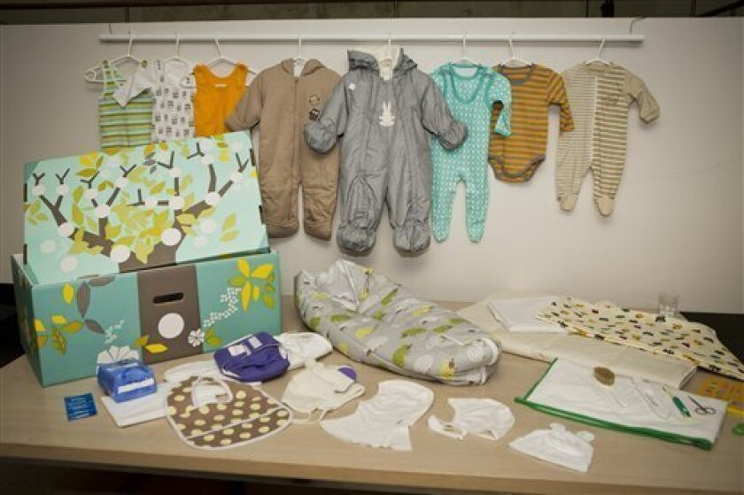 This photo taken on Aug. 15, 2012 shows the contents of the Finnish baby box, in Helsinki, Finland. Finland's social security service has given a baby box to Prince William and former Catherine Middleton, who are expecting their first baby in mid-July. The brightly colored cardboard box doubles as a cot, complete with mattress and sheets, and contains numerous baby items including a sleeping bag, jump suits, socks, pants, hats, bonnets and diapers. Maternity packages have been given to expectant
