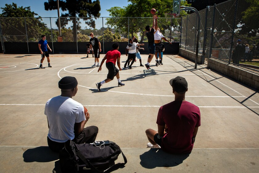Two players sit and watch a pickup basketball game