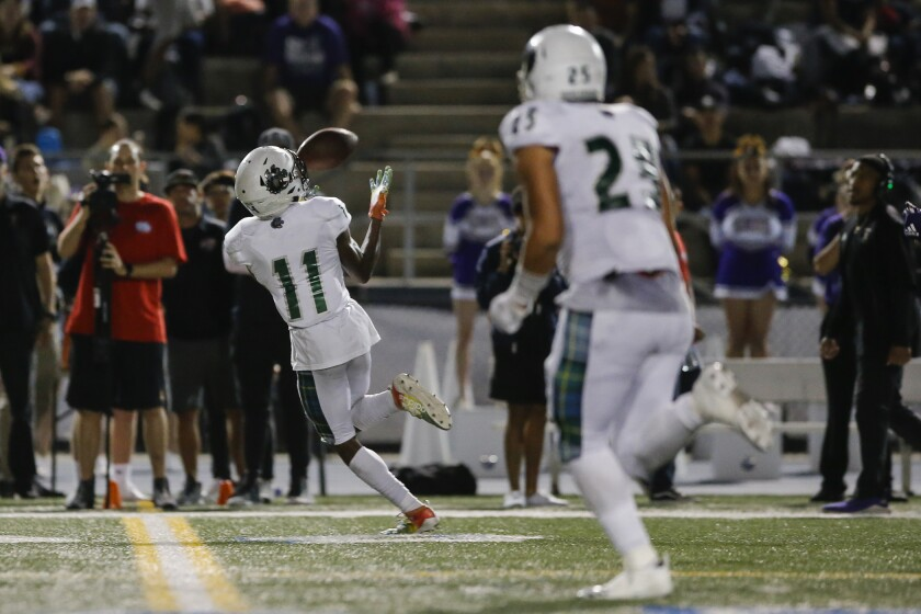 Helix wide receiver Keionte Scott (11) catches a 70-yard touchdown in a game Sept. 20 against St. Augustine.