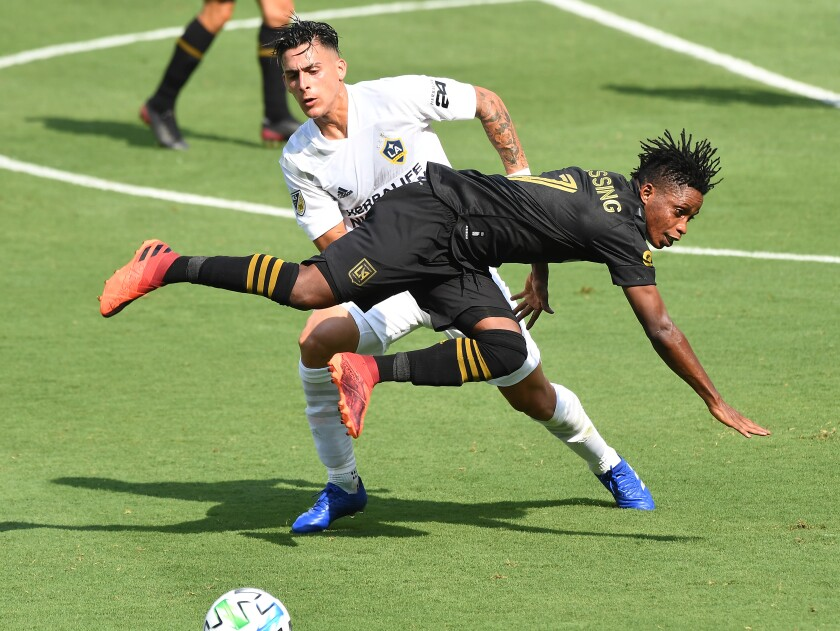 LAFC's Latif Blessing is upended by the Galaxy's Cristian Pavón at  Banc of California Stadium on Aug. 22, 2020.
