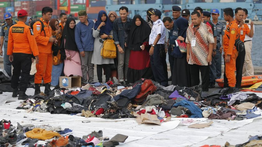 FILE - In this Oct. 31, 2018, file photo, relatives of passengers of a crashed Lion Air jet check pe