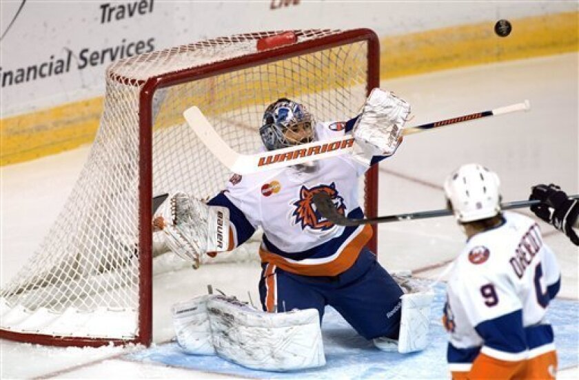 Bridgeport Sound Tigers' Rick DiPietro deflects a shot on goal against the Springfield Falcons during an AHL hockey game Saturday Dec. 5, 2009 in Bridgeport, Conn. DiPietro is returning to playing in his first game after being injured while playing for the Long Island Islanders. (AP Photo/Douglas Healey).