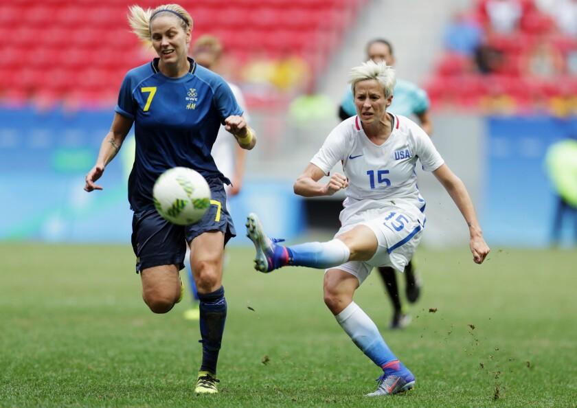 Megan Rapinoe, right, kicks the ball past Sweden's Lisa Dahlkvist at the Olympics on Aug. 12. Rapinoe knelt during the national anthem on Sunday.