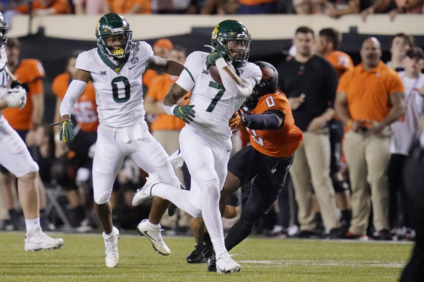 Baylor running back Abram Smith (7) carries past Oklahoma State cornerback Christian Holmes (0) on a 55-yard touchdown run in the second half of an NCAA college football game, Saturday, Oct. 2, 2021, in Stillwater, Okla. (AP Photo/Sue Ogrocki)