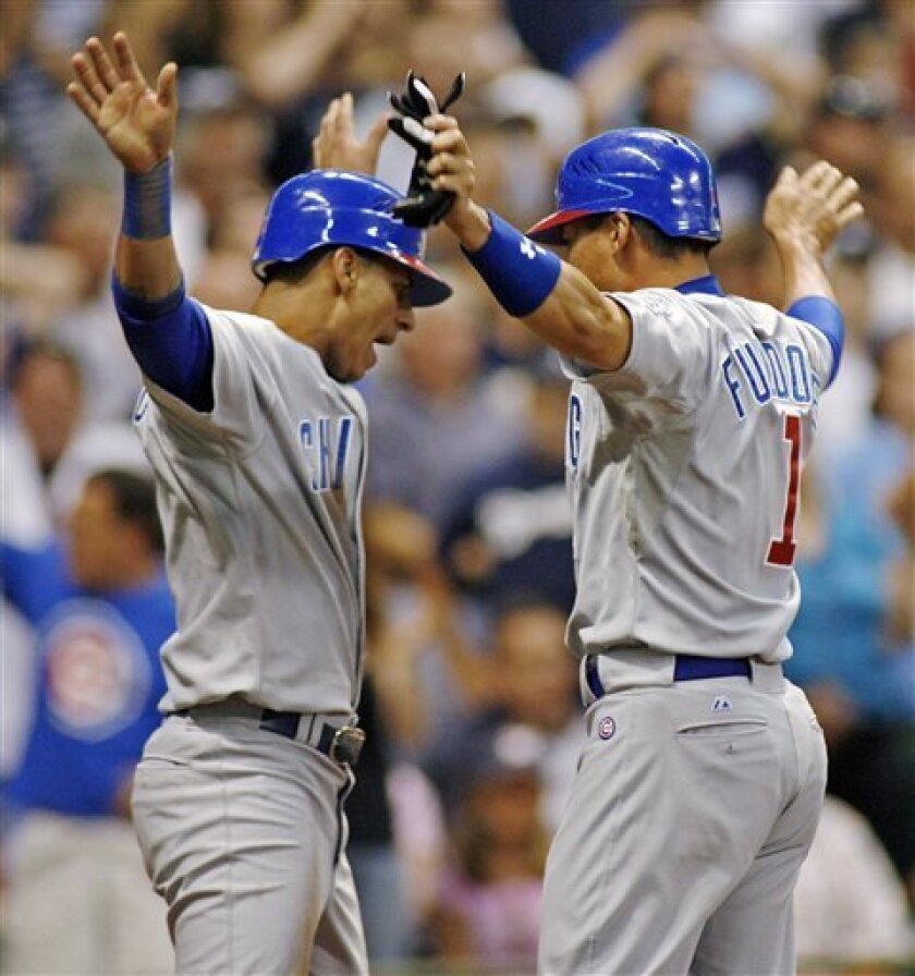 Chicago Cubs' Kosuke Fukudome, right, and Ronny Cedeno celebrate after scoring off on a single by Derrek Lee against the Milwaukee Brewers in the seventh inning of a baseball game Monday July 28, 2008, in Milwaukee. (AP Photo/Darren Hauck)