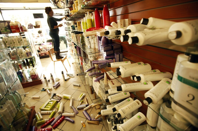 Roya Alagh, manager of Sherman Oaks Beauty Center on Ventura Boulevard in Sherman Oaks, cleans up hair care products knocked to the floor by an earthquake that struck Los Angeles about 6:25 a.m. Monday.