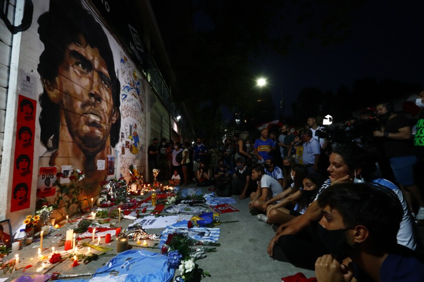 Soccer fans hold a vigil for Diego Maradona outside the stadium of Argentinos Juniors soccer club.