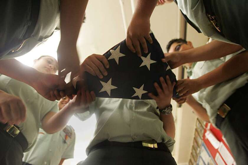 "Critics of the new American history Advanced Placement exam say it teaches a ""revisionist"" view of the nation's history. Above, JROTC students at Roosevelt High School fold an American flag."