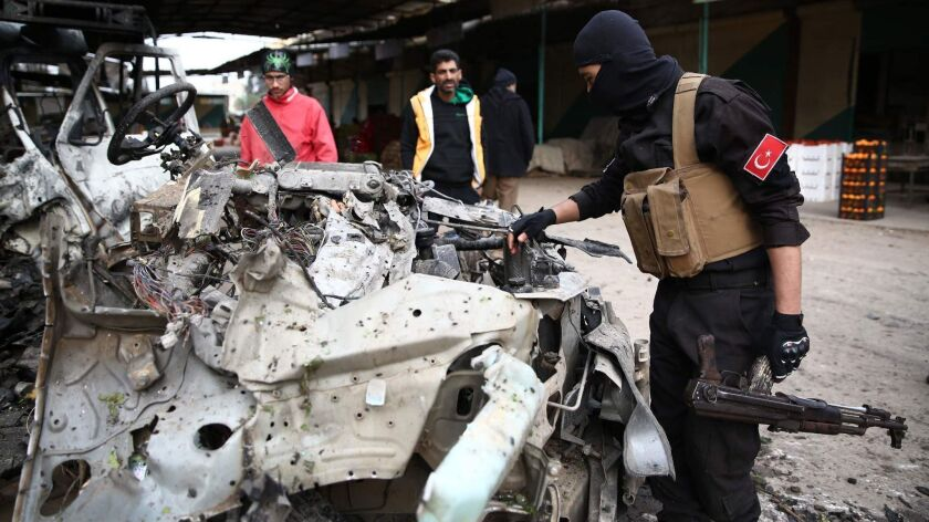 A pro-Turkish Syrian fighter inspects the remains of a car that reportedly exploded in a market in the northwestern Syrian city of Afrin, killing at least eight.