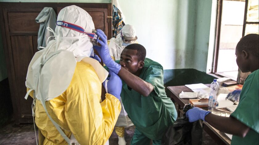 In this photo taken Saturday, May 12, 2018, health workers don protective clothing as they prepare t