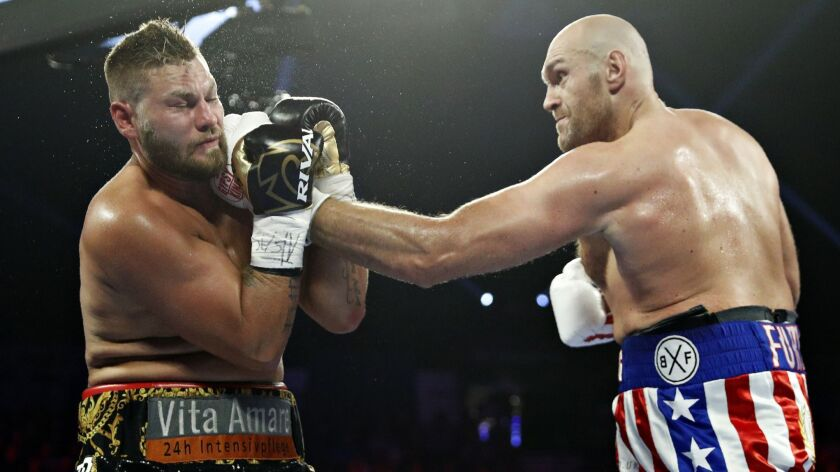 Tyson Fury, of England, lands a left to Tom Schwarz, of Germany, during a heavyweight boxing match S