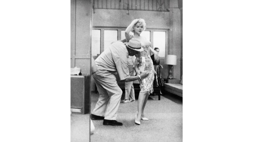 """Costume designer Orry-Kelly dresses Marilyn Monroe for """"Some Like It Hot"""" in a still from the documentary """"Women He's Undressed."""""""
