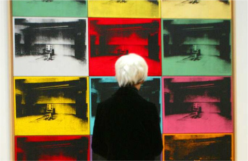 A museum visitor dressed as Andy Warhol passes a painting of electric chairs at a 2002 MOCA exhibition.