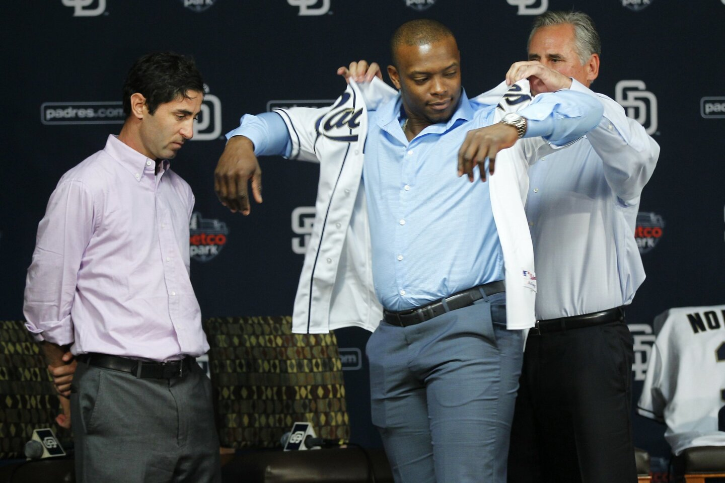 Padres General Manager A.J. Preller, watches as Manager Bud Black helps Justin Upton with his jersey at Petco Park.