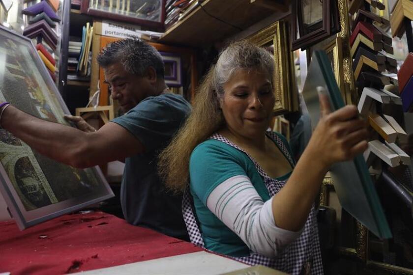 La mexicana Martha de la Barrera (d) mientras trabaja enmarcando cuadros este, jueves 7 de marzo de 2019, en Ciudad de México (México). EFE