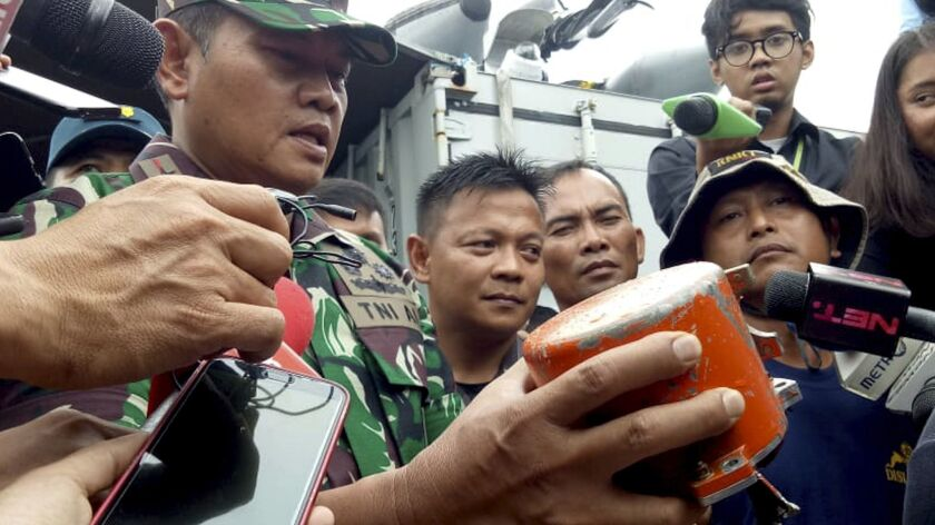 Indonesian Navy Commander Rear Admiral Yudo Margin shows the recovered cockpit voice recorder of Lio