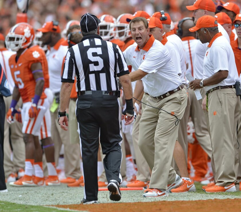 FILE - In this Sept. 12, 2015, file photo, Clemson head coach Dabo Swinney disputes a call by an official during the second half of an NCAA college football  game against Appalachian State, in Clemson, S.C. All eyes around the Atlantic Coast Conference will be on officials this weekend. No one want