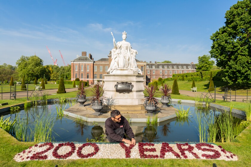 Gardener works on floral display at Kensington Palace