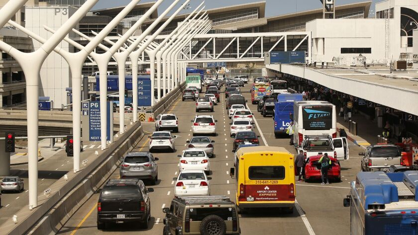 Motorists make their way through Los Angeles International Airport on May 31. Car-sharing company Turo is suing LAX, claiming the airport is under pressure from Enterprise Rent-a-Car to force Turo to pay the same fees that rental car companies pay.