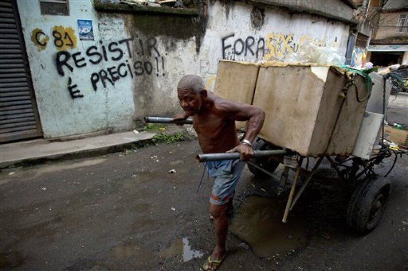 "In this photo taken Jan. 31, 2012, a man pushes a cart with goods to recycle past a graffiti that reads in Portuguese ""We must resist"" in the Favela do Metro shantytown in Rio de Janeiro, Brazil. Residents of communities like Metro, located on the surroundings of the Maracana stadium, are being pushed out of their homes to make way for new roads, Olympic venues, and other projects as part of preparations to host the 2014 World Cup and the 2016 Olympics. (AP Photo/Victor R. Caivano)"