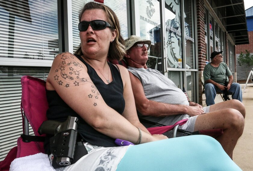 Crystal Tewelow, armed with a loaded gun on her hip, talks with fellow gun owners in front of an Army and Marine recruitment center on Wednesday, July 22, 2015, in Hiram, Ga. Tewelow was one of several armed citizens who held watch at the recruitment center in response to the deadly shooting at a similar facility in Chattanooga, Tenn. (AP Photo/Ron Harris)