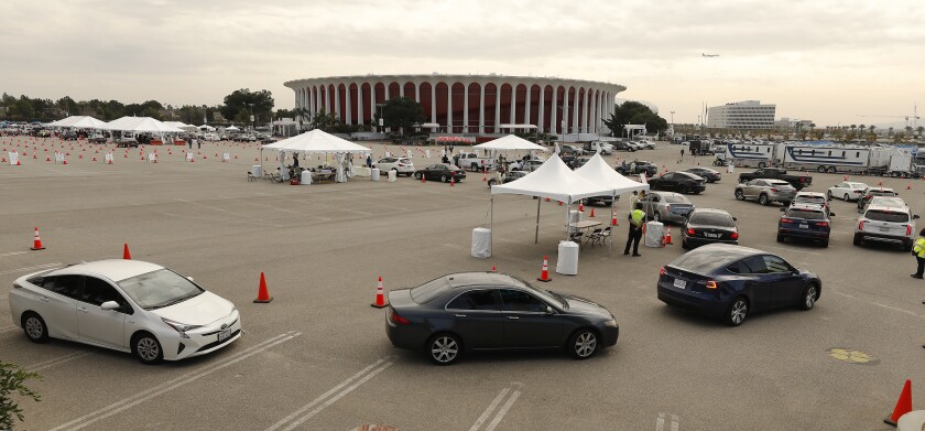 Vehicles line up at the Forum in Inglewood for vaccines