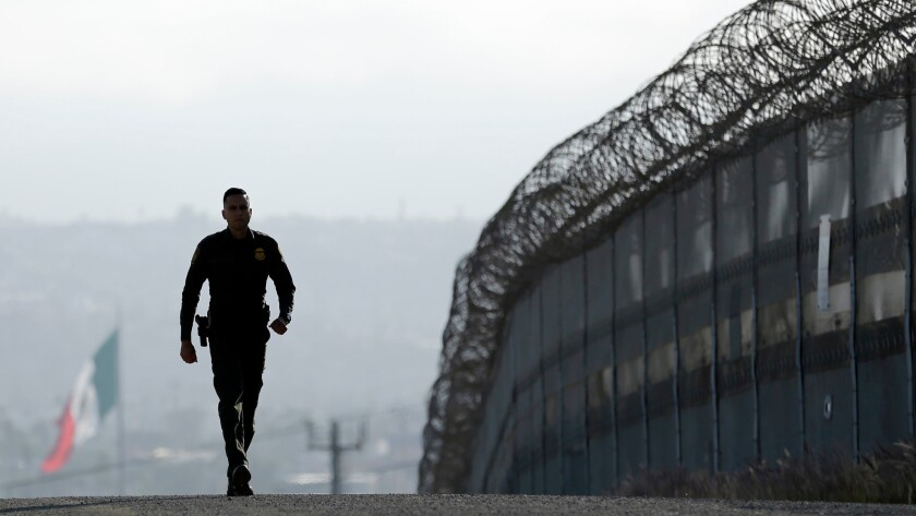 A Border Patrol agent walks near the secondary fence separating Tijuana and San Diego.