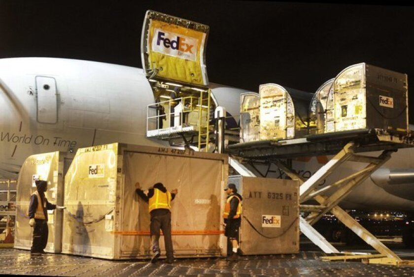 Containers filled with packages are loaded on a cargo plane at the LAX FedEx facility.