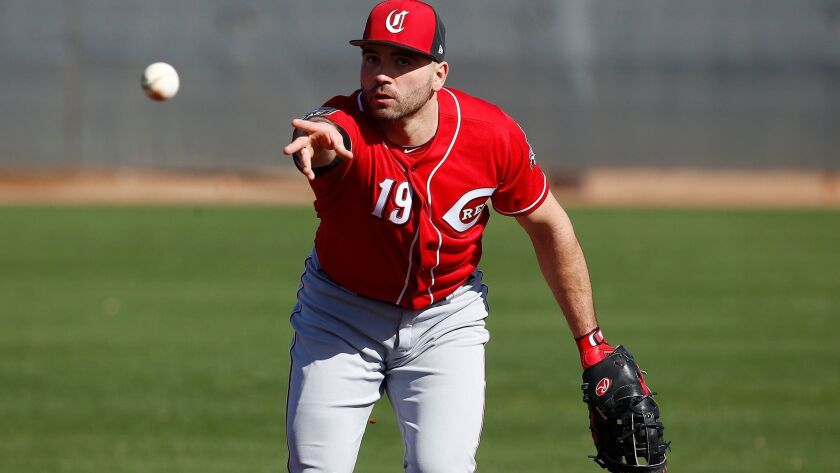 Reds first baseman Joey Votto flips the baseball to first base at the Reds spring training facility, Tuesday, Feb. 20, 2018, in Goodyear, Ariz.