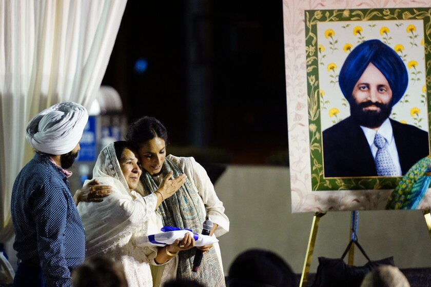 Valarie Kaur, right, of the Revolutionary Love Project, hugs Harjinder Kaur Sodhi, the widow of Balbir Singh Sodhi, middle, as Balbir's brother Rana Singh Sodhi, left, looks on at a memorial service on the 20th anniversary of the murder of Balbir Singh Sodhi Wednesday, Sept. 15, 2021, in Mesa, Ariz. Sikh businessman Balbir Singh Sodhi was helping plant a flower bed at his Arizona gas station when he was shot dead by a man seeking to avenge 9/11. Mistaken for an Arab Muslim because of his turban and beard, Sodhi was the first person to die in a wave of bias crimes unleashed by the attacks. (AP Photo/Ross D. Franklin)
