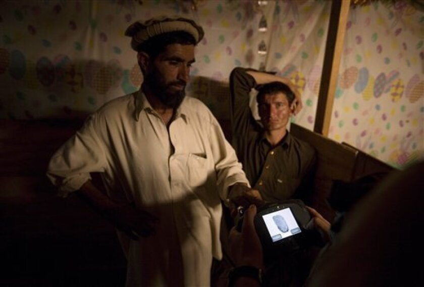 A local Afghan villager who goes by the name of Manam, has his fingerprint scanned to be registered as a community security guard by a soldier with the U.S. Army's 2nd Battalion 27th Infantry Regiment based in Hawaii, Thursday, July 7, 2011 at Combat Outpost Pirtle King in Kunar province, Afghanistan. (AP Photo/David Goldman)