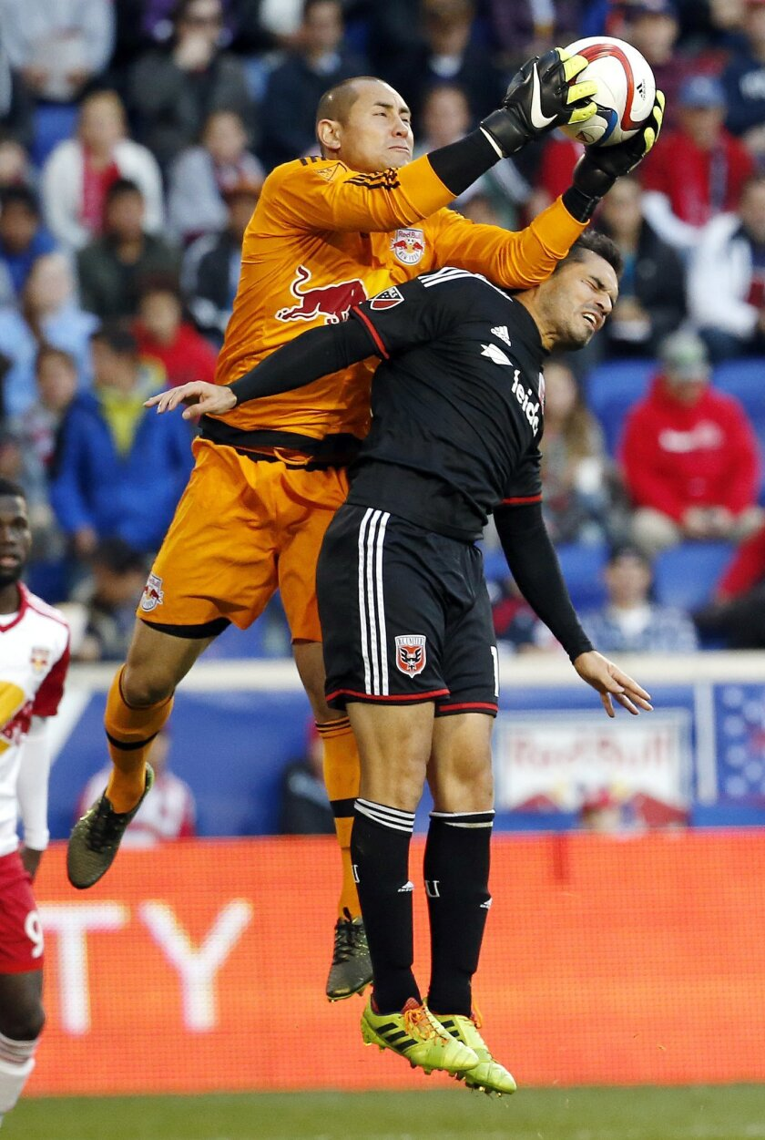 New York Red Bulls goalkeeper Luis Robles, left, grabs the ball as D.C. United forward Fabian Espindola challenges during the second half of an MLS playoff soccer match, Sunday, Nov. 8, 2015, in Harrison, N.J. (AP Photo/Julio Cortez)