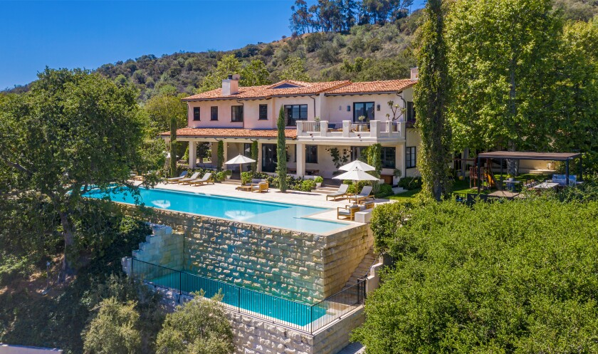 A stucco and tile home with two swimming pools.